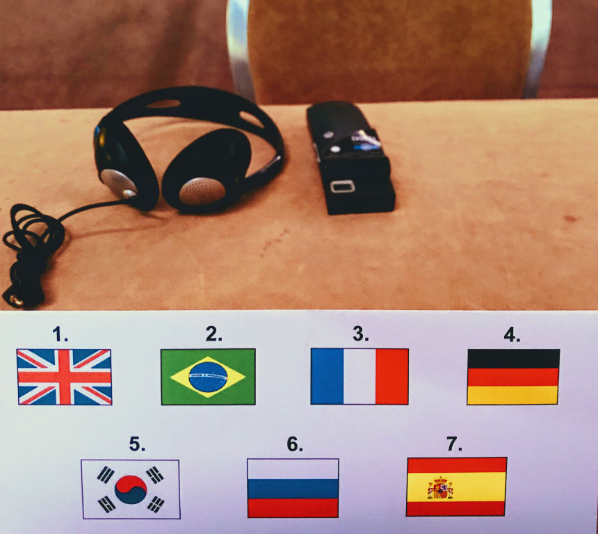 Interpretation equipment on desk with flags identifying languages being interpreted